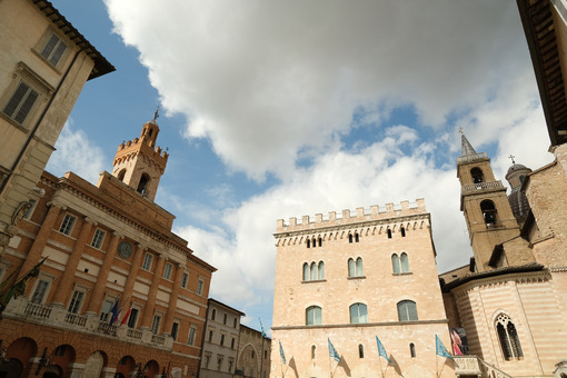 Piazza della Repubblica in Foligno with the town hall and canonics. The ancient palaces lit by the sun with cloudy sky. - LEphotoart.com