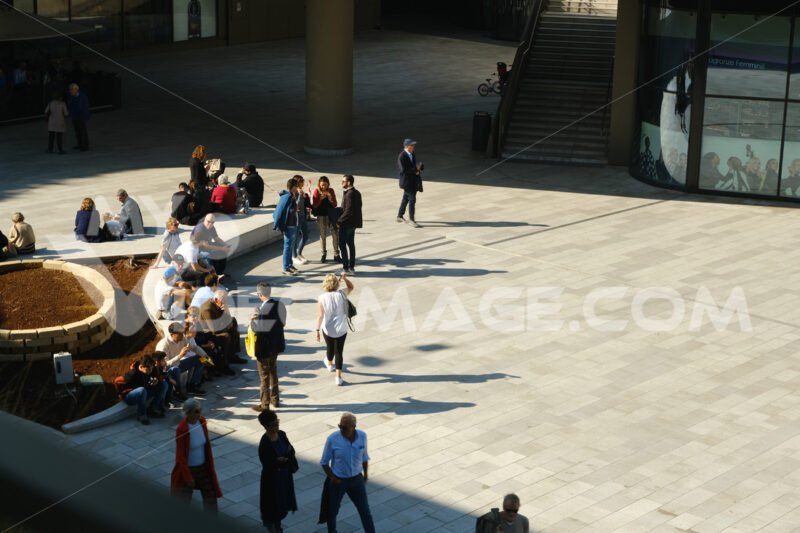 Piazza with entrance to the Citylife shopping center in Milan. People sitting on stone benches and walking. - MyVideoimage.com