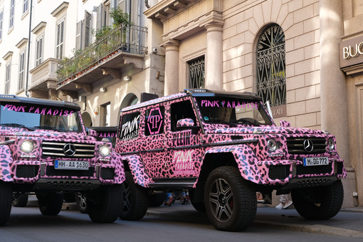 Pink off-road vehicles run along Via Montenapoleone in Milan. Luxury shops and cars in the fashion week. Foto automobili. Cars photos.