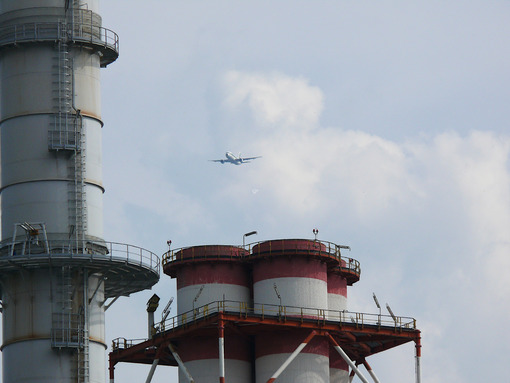 Plane flies over the chimneys of a power plant - MyVideoimage.com