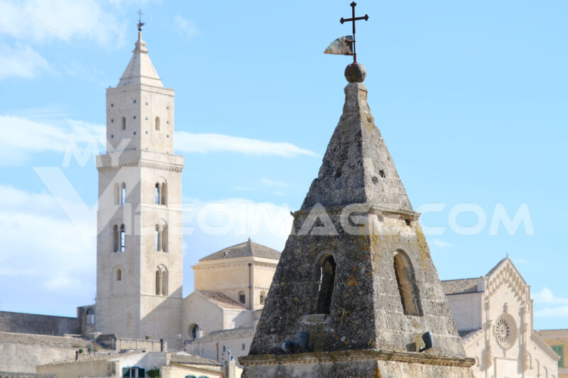 Point of two bell towers and church in the ancient city of Matera in Italy. Construction with blocks of tufa stone. Chileo blue with clouds. - MyVideoimage.com