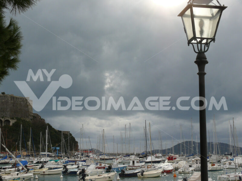 Port of Lerici with moored boats. Cloudy sky. The sun illuminates a street lamp. - MyVideoimage.com