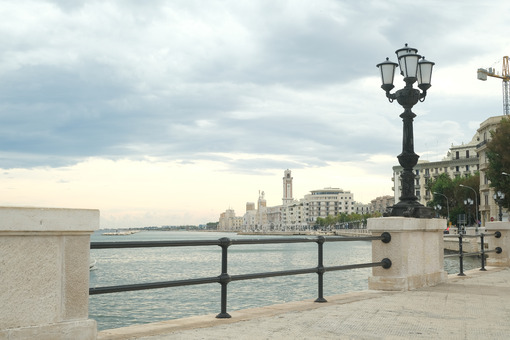 Promenade of Bari with the buildings of the Murattiano village. A parapet and a street lamp on the road that runs along the sea. - MyVideoimage.com | Foto stock & Video footage