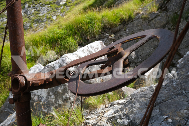Puleggia in ferro. Old iron pulley used in marble quarries to cut stone. Foto stock royalty free. - MyVideoimage.com | Foto stock & Video footage