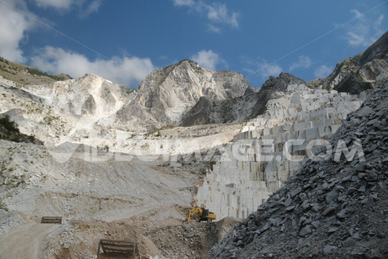 Quarries panorama. Carrara Marble. Panorama of a white Carrara marble quarry in Tuscany. Mountains of the Apuan Alps, blue sky and cloud. - MyVideoimage.com | Foto stock & Video footage
