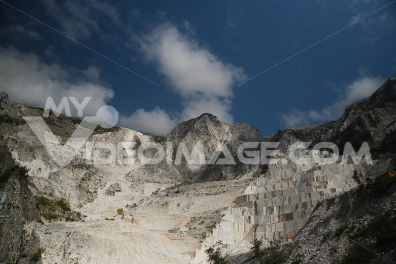 Quarry panorama. Panorama of a white Carrara marble quarry in Tuscany. Mountains of the Apuan Alps, blue sky and cloud. - MyVideoimage.com | Foto stock & Video footage