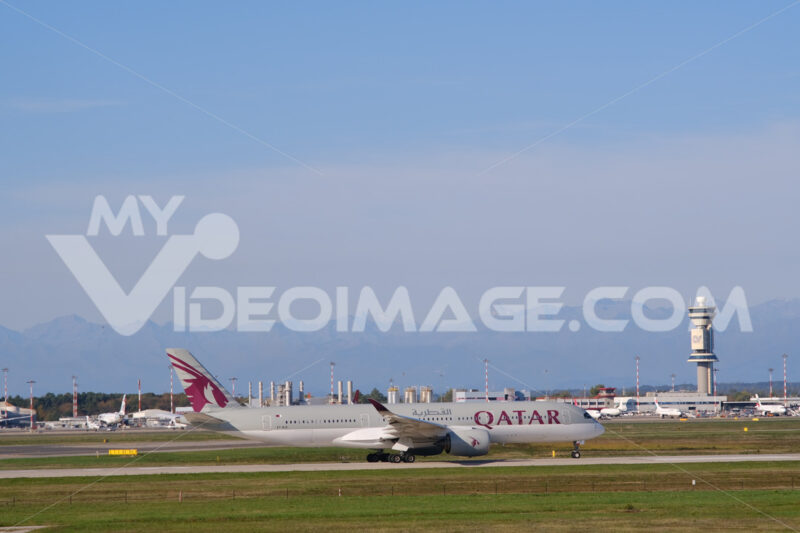 Quatar Airbus A350-941 airplane taxiing on the Malpensa airport runway. In the background the control tower. - MyVideoimage.com