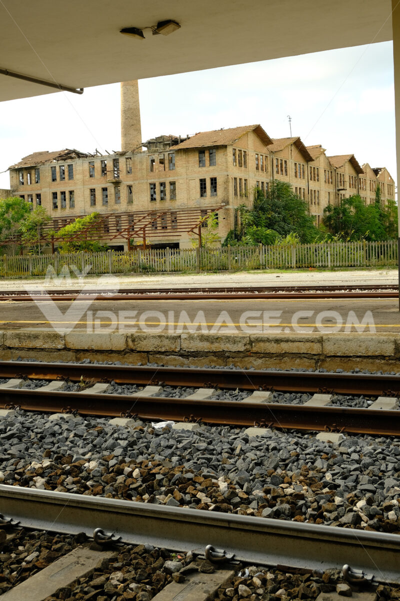 Railway station with tracks and in the background an old abandoned factory. Foto Stazione. Station photo
