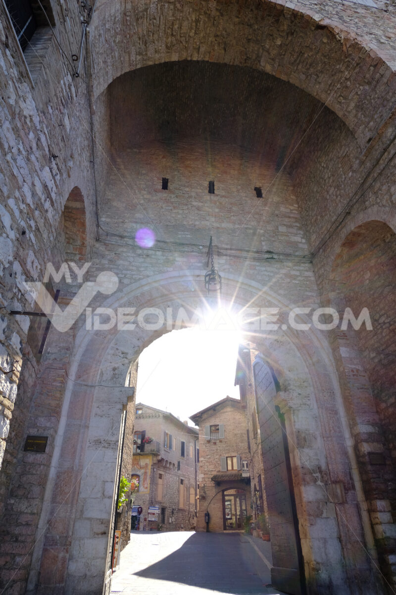 Ray of sun enters from the ancient San Pietro gate in Assisi. Made with mixed brick and stone masonry. - MyVideoimage.com