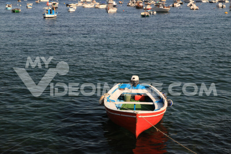 Red-colored boat anchored at the sea port. A small fishing boat. - MyVideoimage.com