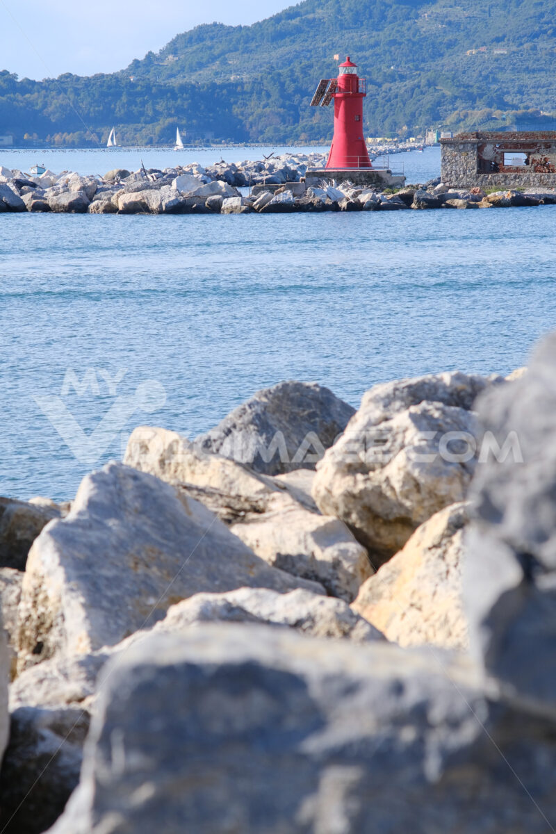 Red lighthouse on the rocks at the entrance to the port of La Spezia. - MyVideoimage.com