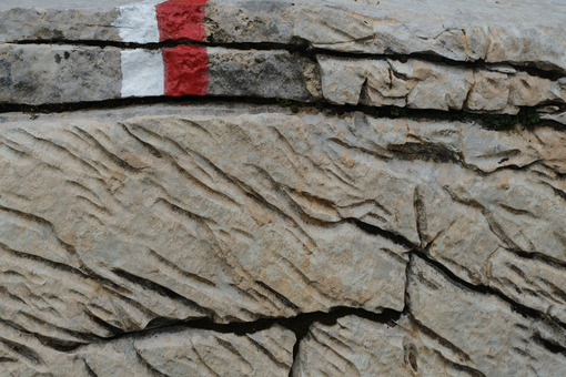 Red mark on the stone. Stone carved from water erosion with a red and white trail mark. Stock photos. - MyVideoimage.com | Foto stock & Video footage