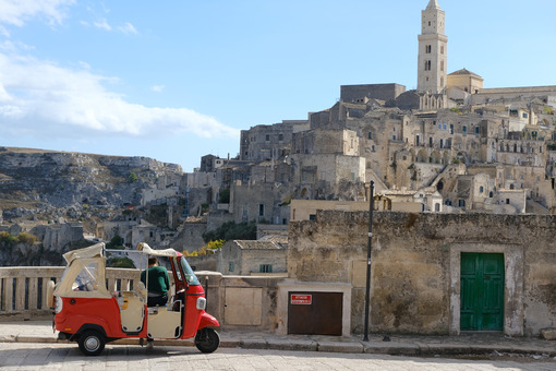 Red taxi made with a Piaggio APE. In the background the city of Matera. - MyVideoimage.com