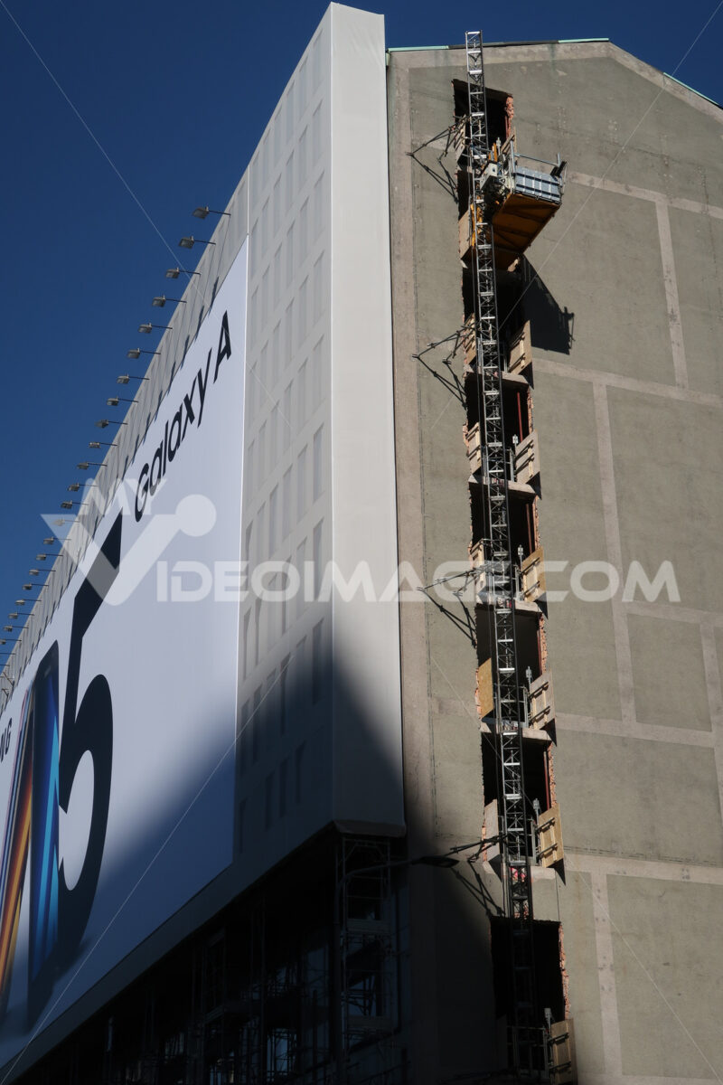 Renovation of an office building in Milan. Construction site freight elevator. Advertising of a smartphone posted on the facade. - LEphotoart.com