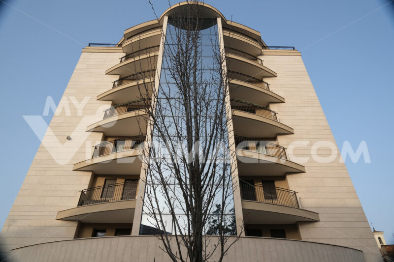 Residential BUilding. Busto Arsizio. Modern tower building set in front of a leafless tree. On the central part of the building you can see the vertical window of the stairwell. - MyVideoimage.com | Foto stock & Video footage
