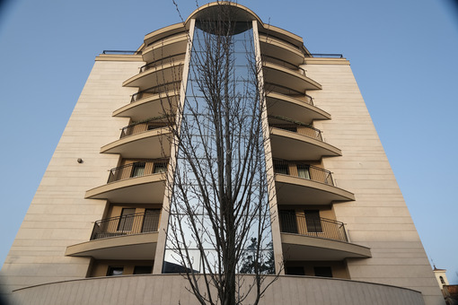 Residential BUilding. Busto Arsizio. Modern tower building set in front of a leafless tree. On the central part of the building you can see the vertical window of the stairwell. - MyVideoimage.com   Foto stock & Video footage
