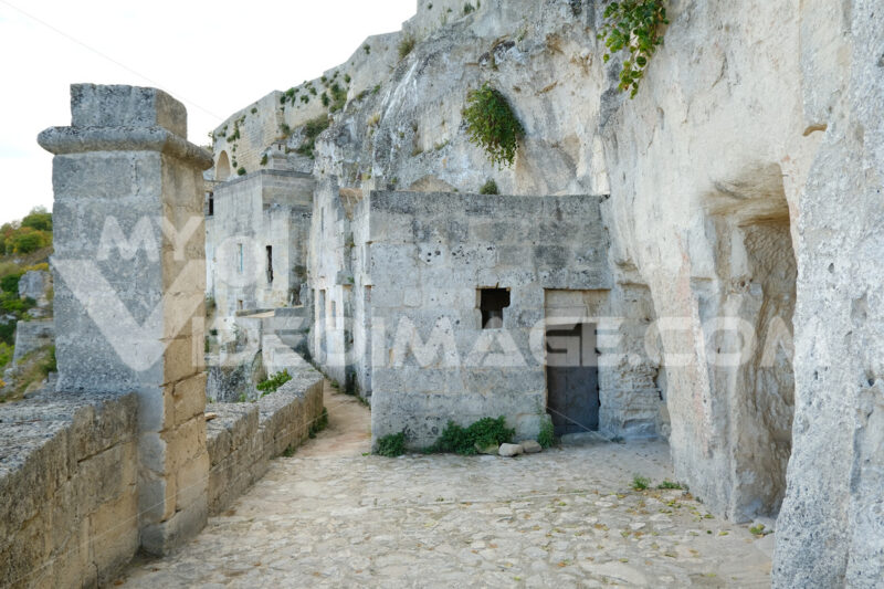 Road and facades of the Sassi of Matera. Doors and windows of ancient underground houses carved into the tuff rock. - MyVideoimage.com