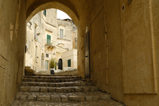 Road in the ancient city of Matera. Paving with beige stone and covering with arch and vault. - MyVideoimage.com