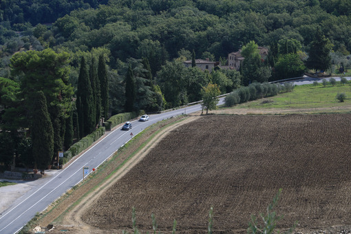 Road with cars on the Chianti hills. Cultivated fields and farmhouses in the Tuscan countryside near Florence. - MyVideoimage.com