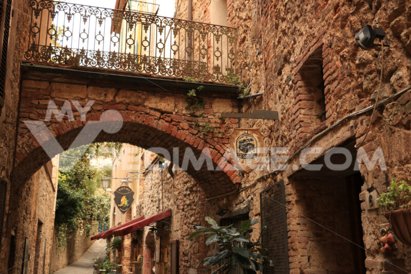 Romantic restaurants in a street of Massa Marittima. An alley with restaurant signs and tables with chairs. - MyVideoimage.com | Foto stock & Video footage