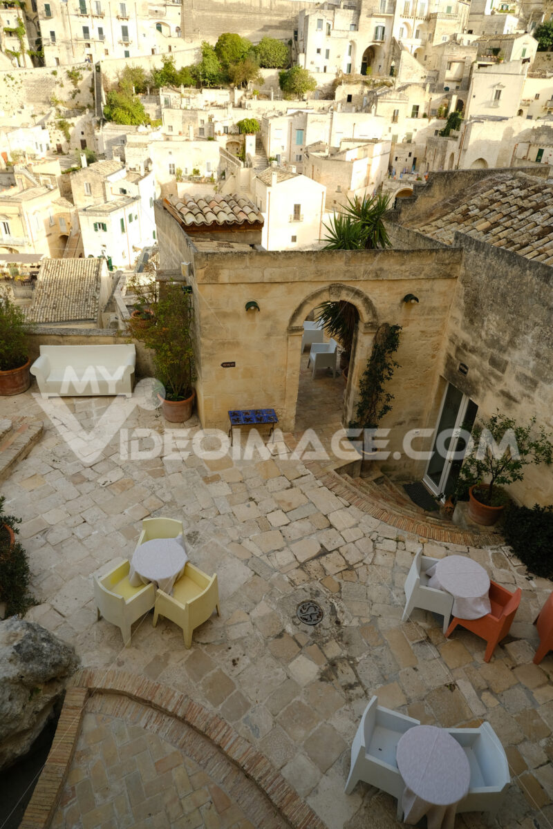 Roofs of houses in the Sassi of Matera transformed into hotels. Panoramic terrace with sofa and chair in white plastic. - MyVideoimage.com