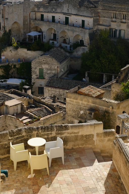 Roofs of houses in the Sassi of Matera transformed into hotels. Panoramic terrace with sofa and chair in white plastic. - LEphotoart.com