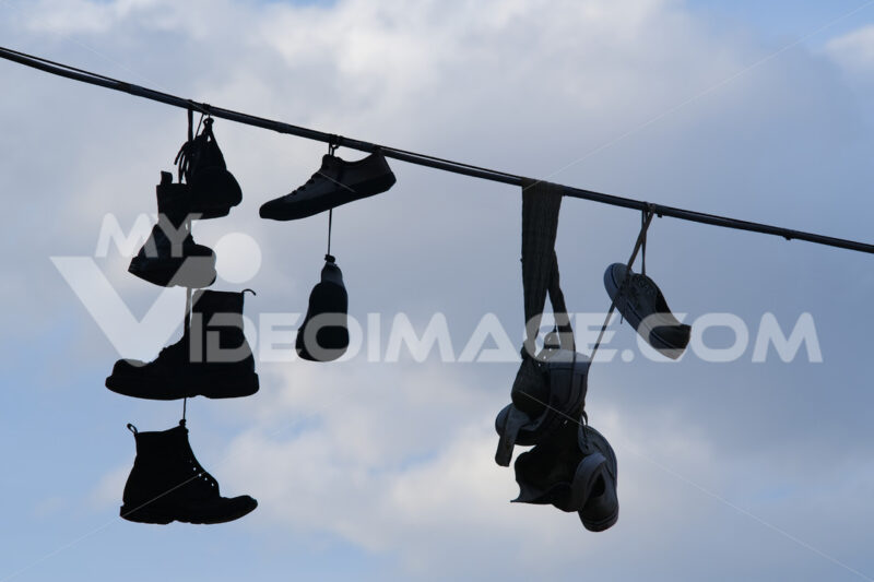 Row of shoes hanging from an electric cable against the backdrop of sky with sunshine. - MyVideoimage.com