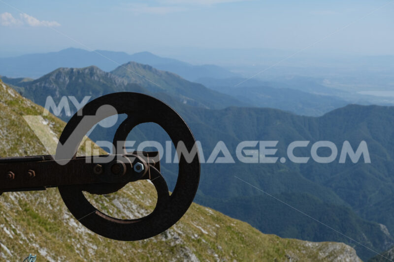 Ruota in ferro sulla montagna. Alpine panorama on the Apuan Alps in Alta Versilia. Monte Corchia. Foto stock royalty free. - MyVideoimage.com | Foto stock & Video footage