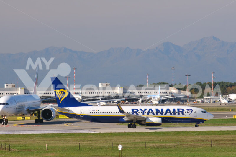 Ryanair Boeing 737-800 airplane on the Malpensa airport runway. Behind Easyjet Airbus airplane lands on the Malpensa airport runway. - MyVideoimage.com