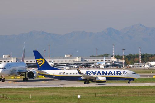 Ryanair Boeing 737-800 airplane on the Malpensa airport runway. Behind Easyjet Airbus airplane lands on the Malpensa airport runway. - MyVideoimage.com