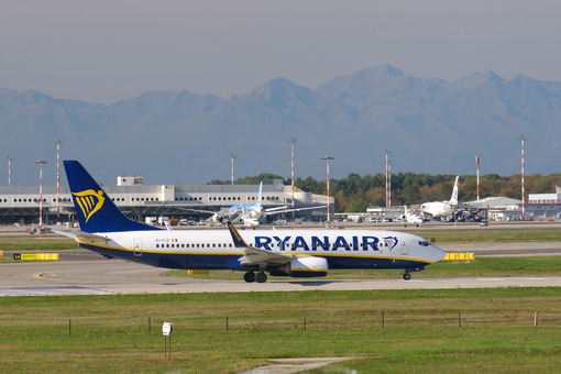 Ryanair Boeing 737-800 airplane on the Malpensa airport runway. In the background the buildings of Terminal Cargo and parked airplanes. - MyVideoimage.com