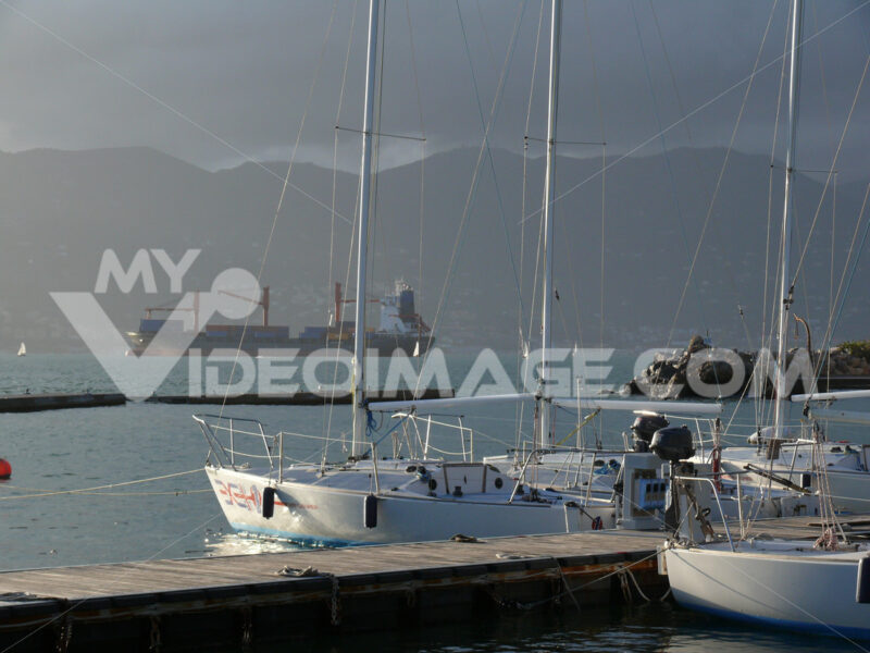 Sailboats anchored at the pier in the Gulf of La Spezia. In the background cargo ship. Sun and clouds. - MyVideoimage.com