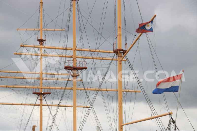 Sailing ship masts with Dutch flag. Sky background with clouds. - MyVideoimage.com