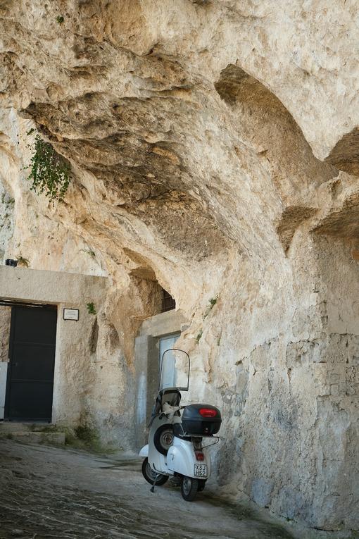 Scooter Vespa Piaggio parked in a cave of the Sassi of Matera in Basilicata. - MyVideoimage.com