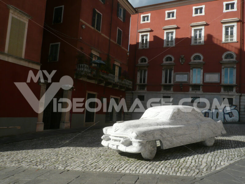 Sculpture depicting a Cadillac car made of white Carrara marble displayed in a town square. - MyVideoimage.com