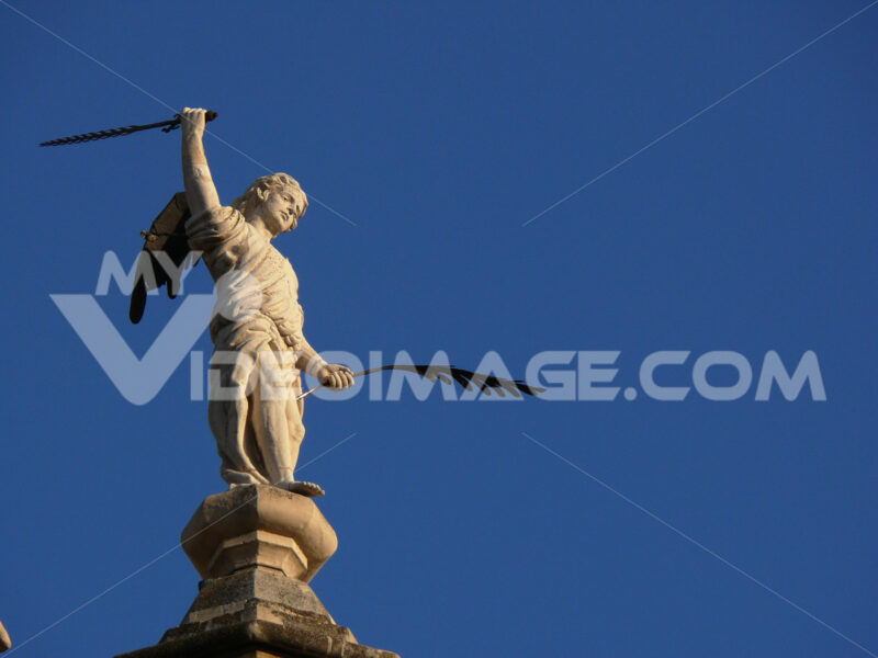 Sculpture of angel with pen and sword. - MyVideoimage.com