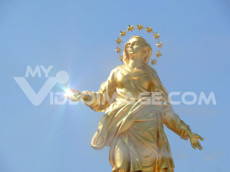 Sculpture representing the Madonna of the Milan Cathedral. Reflections of the sun. Copy - MyVideoimage.com