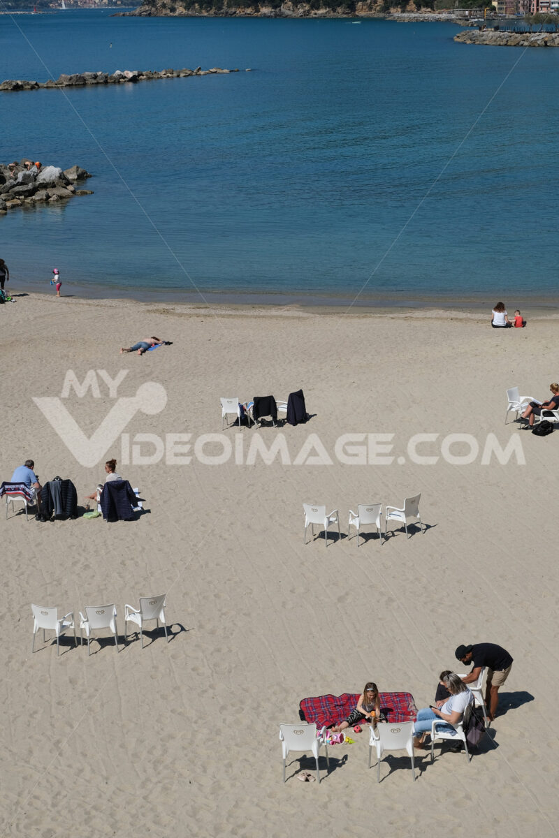 Sea and pandemic. People on the beach by the sea in Liguria during the Covid-19 pandemic. Stock photos. - MyVideoimage.com | Foto stock & Video footage