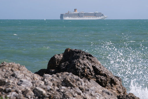Sea cliff with waves and cruise ship. The waves of the Ligurian sea crash on the rocks. - MyVideoimage.com | Foto stock & Video footage