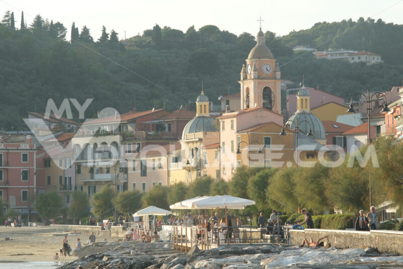 Sea village of San Terenzo of Lerici. Houses and church near the sea with people on the beach and rocks. - MyVideoimage.com