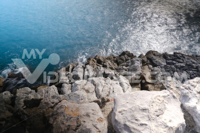 Sea waves break on the rocks near Cinque Terre. Sea of the channel between the Palmaria Island and the Portovenere in Liguria. - MyVideoimage.com