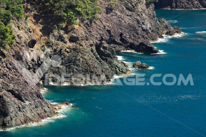 Sea waves break on the rocks of the Ligurian mountain.  Near the Cinque Terre a seascape with blue sea and dark red rocks. Village of Framura. - MyVideimage.com