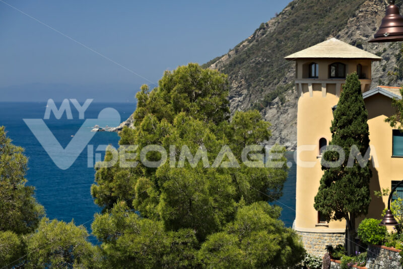 Seascape with house turret near the Cinque Terre. In the village of Framura a villa with a tower overlooking the blue sea and dense Mediterranean vegetation. - MyVideimage.com