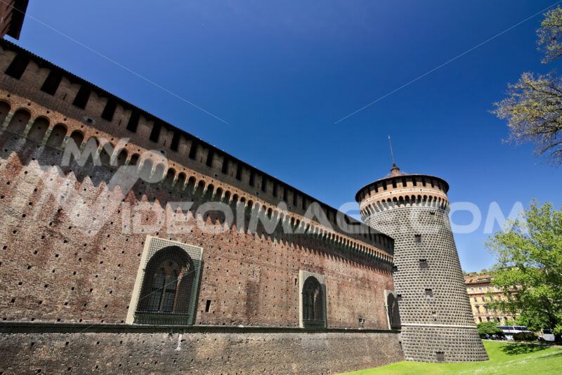 Sforza Castle in Milan. Cylindrical tower and walls. The Castle with the walls and the background of the blue sky of a spring day. - MyVideoimage.com
