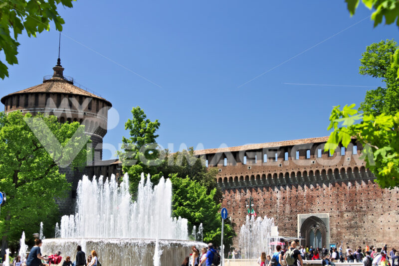 Sforza Castle in Milan. The red brick walls and the tower. Many people walk near the Castle. In the foreground the fountain and the trees. - MyVideoimage.com