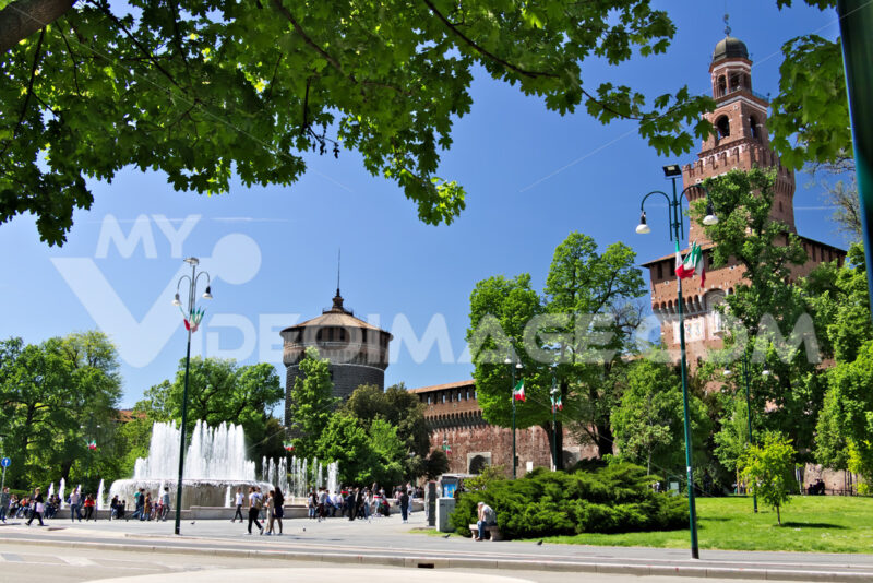 Sforza Castle in Milan. The red brick walls and the tower. Many people walk near the Castle. In the foreground the fountain and the trees. Città italiane. Italian cities.