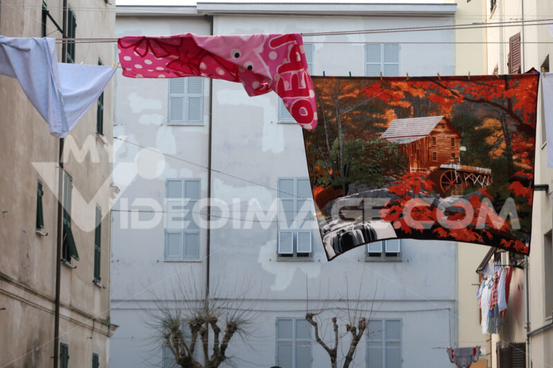 Sheets decorated with images hung out to dry on a wire stretched between two buildings in La Spezia. - MyVideoimage.com