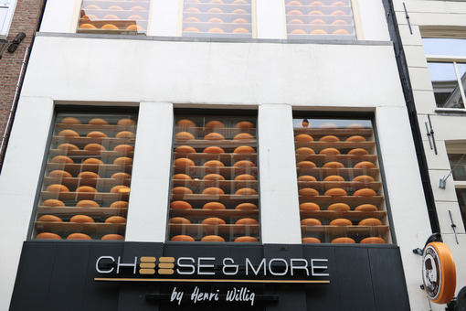 Shop showcase with large cheeses on display. Shop signboard. - MyVideoimage.com