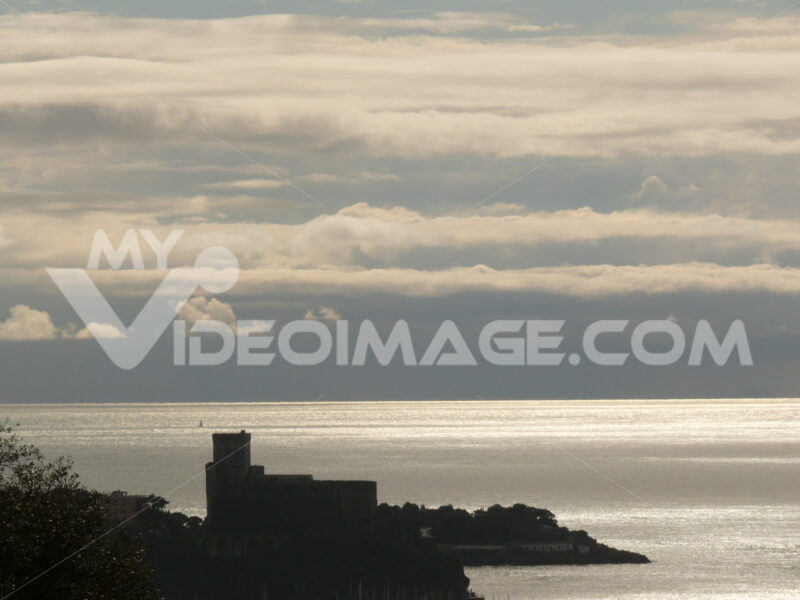 Silhouette of the castle of Lerici at sunset. Sky with clouds and sea of gold color. - MyVideoimage.com