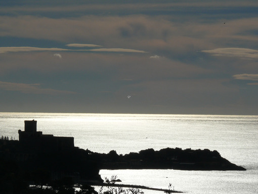Silhouette of the castle of Lerici at sunset. Sky with clouds and sea of gold color. Foto sfondo mare. - MyVideoimage.com